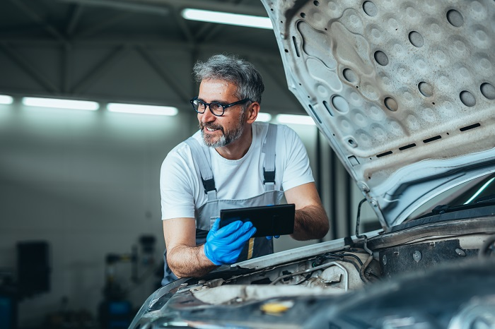 worker using tablet for car diagnostic service